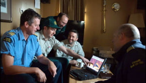 Parks Canada's Ryan Harris (second from left) shows Canadian Coast Guard Ship Sir Wilfrid Laurier's Commanding Officer Bill Noon (far left) the side-scan sonar image of the wreck, with Marc-André Bernier (third from left), Jonathan Moore (fourth from left) and Chief Officer Rich Marriott (at far right) (Photo: Theresa Nichols, Fisheries and Oceans Canada).