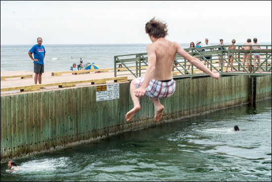 Leaping off the pier at Basin Head Provincial Park's beach is a risky act but few of the excited divers pay attention to the warning signs when they visit the PEI attraction. (Adrian Brijbassi/Vacay.ca)