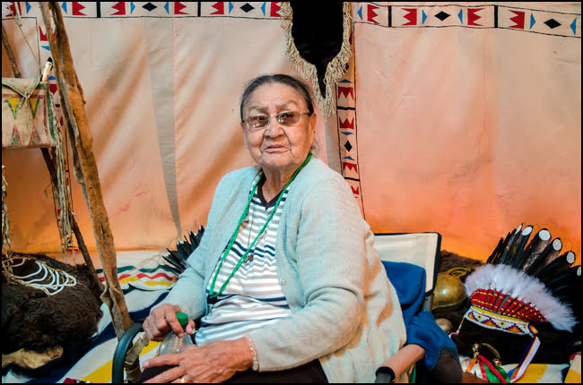 Margaret of the Siksaka Nation welcomes visitors into her tepee home at the Indian Village. (Julia Pelish/Vacay.ca)